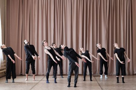 Horizontal shot of professional dancers wearing black outfit rehearsing their new contemporary dance 免版税图像