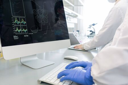 Horizontal shot of two unrecognizable scientists wearing white coats gloves working in laboratory using modern computers 写真素材