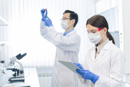 Two young scientists wearing protective masks and gloves working on new medicaments in modern laboratory