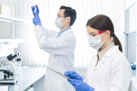 Two professional pharmacologists wearing protective masks, gloves and eyeglasses working on medicaments in modern laboratory
