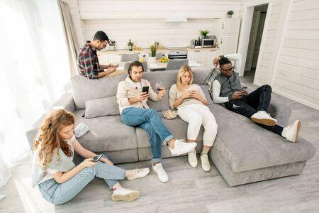 Disparo horizontal de jóvenes modernos viendo algo en sus teléfonos inteligentes en lugar de interactuar entre sí Foto de archivo