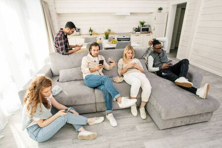 Horizontal shot of modern young people watching something on their smartphones instead of interacting with each other Archivio Fotografico