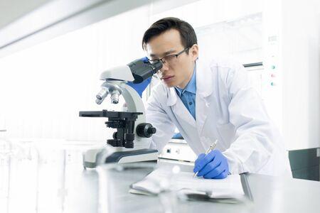 Asiatischer Mediziner mit weißem Kittel, der das Exemplar mit dem Mikroskop untersucht, horizontales Porträt