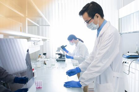 Two young doctors in white coats working in modern laboratory examining specimens, side view shot