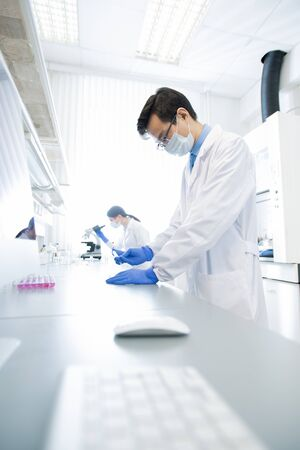 Vertical shot of two unrecognizable doctors in white coats working in modern laboratory examining specimens 写真素材