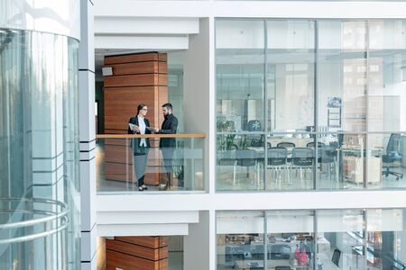 Young office workers standing on balcony of business center and sharing ideas for new project