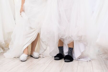 Horizontal shot of two funny unrecognizable women wearing wedding dresses and slippers