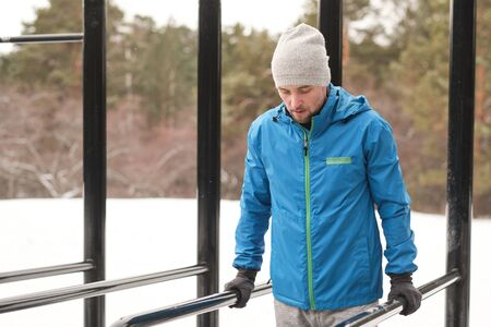 Concentrated young man in hat and jacket looking down while keeping body on parallel bars