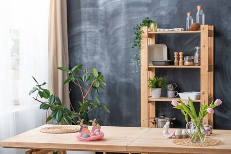 Kitchen interior with Easter decorations and flowers in vase on table, crockery on shelves against blackboard Stockfoto