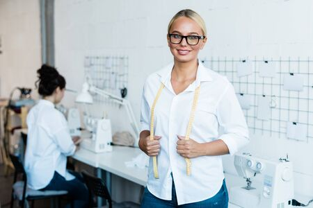 Happy young blonde seamstress with measuring tape looking at you