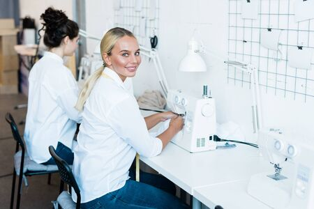 Young cheerful seamstress in jeans and white shirt looking at you during work