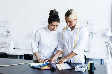 Two young female fashion designers consulting about choice of fabric