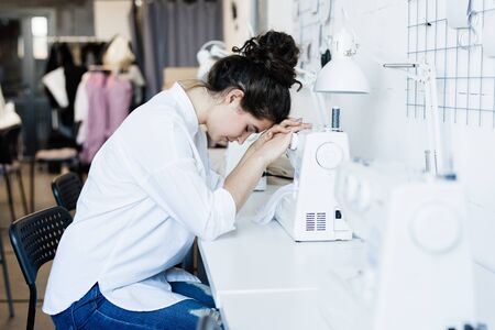 Young tired or sick seamstress keeping her head on electric sewing machine Stock Photo