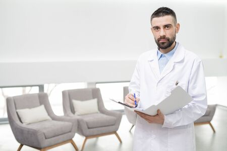 Mid adult dentist in whitecoat making notes in document in dental clinics