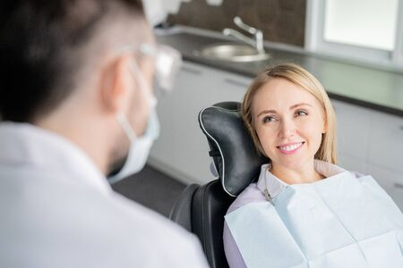 Happy young blonde female patient looking at her dentist with healthy smile