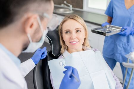 Happy young woman looking at her dentist with toothy smile before examination