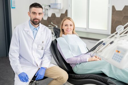 Young professional dentist in gloves and whitecoat and his blond female patient