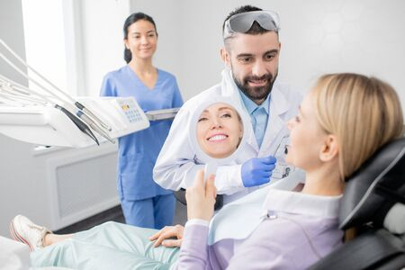 Young smiling woman looking in mirror after procedure of professional whitening