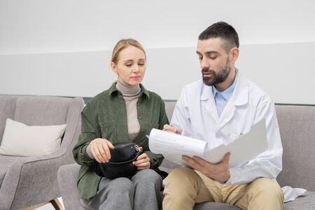 Young woman looking at medical document while dentist filling in questionnaire Zdjęcie Seryjne