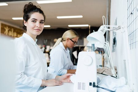 Young attractive seamstress looking at you while sitting by sewing machine Stock Photo