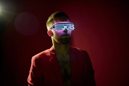 Bearded young man in jacket wearing special futuristic new generated eyewear standing over dark background in isolation