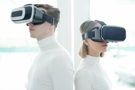 Young people in white sweaters wearing virtual reality goggles standing back to back