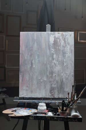 Easel with unfinished picture and set of stuff for professional painting inside classroom of modern arts school or studio