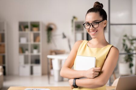 Pretty young elegant secretary in eyeglasses holding notepad or copybook