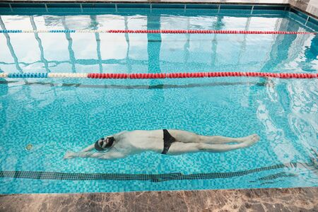 Above of young bearded man in goggles and cap swimming on back in modern pool