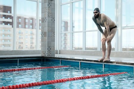 Fit bearded man in swimming goggles and cap standing on edge of poolside and preparing for swimming