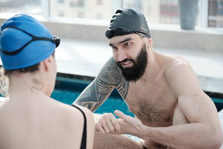 Content young bearded man in swimming cap talking to swimmer while cheering her in poolside Imagens