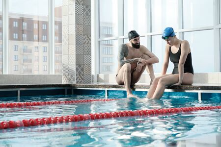 Young bearded man with tattoo sitting on edge of poolside and supporting other swimmer
