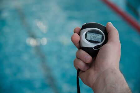 Close-up of unrecognizable coach holding stopwatch while measuring time of swim lap in pool