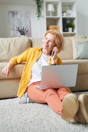Cheerful businesswoman with laptop and talking on the phone.