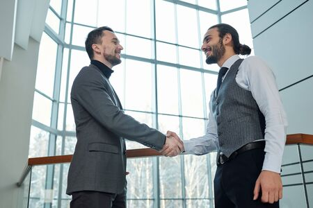 Two young successful busines partners greeting each other by handshake