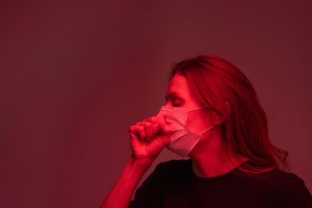 Young sick female with covid19 in protective mask coughing in isolation