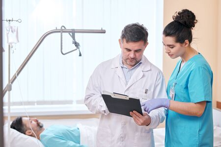 Mature doctor in lab coat standing against patients bad and analyzing health conditions of patient with nurse