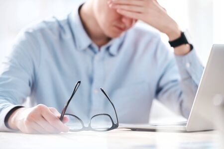 Close-up of puzzled businessman sitting in front of laptop and feeling migraine from exhaustion in office