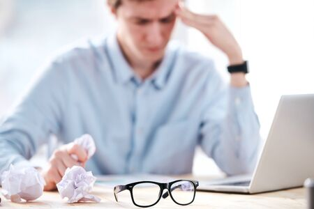 Close-up of young businessman crumpling papers while having not ideas for project in office, focus on eyeglasses in foreground Stock fotó