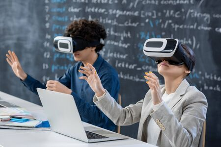 Two teenage students in vr headsets sitting by desk against blackboard and taking part in presentation or seminar in classroom at lesson