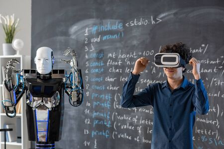 Contemporary guy in vr headset raising hands by blackboard with robot near by Stock Photo