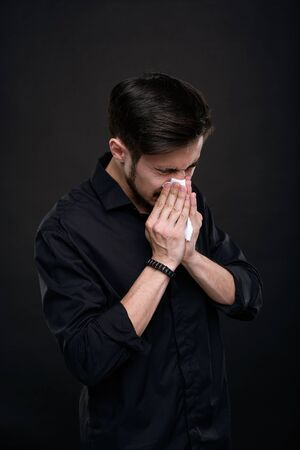 Young brunette man with coronavirus or cold symptom sneezing in napkin against black background