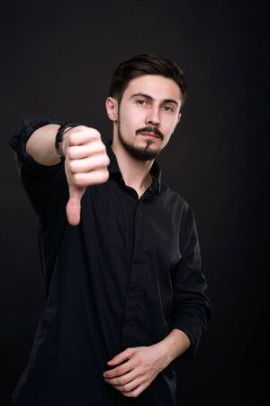 Handsome young man in black shirt showing thumb down while giving bad grade against isolated dark background
