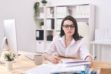 Young serious businesswoman looking at financial paper while making notes