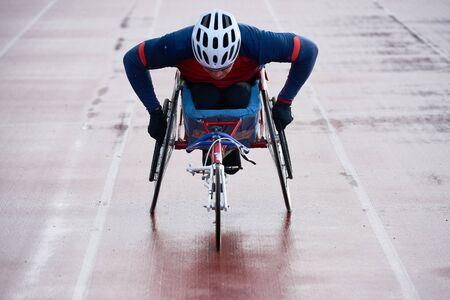 Preparing for wheelchair marathon. Close-up view of paraplegic male athlete training speed while racing in sport wheelchair on outdoor track Stockfoto