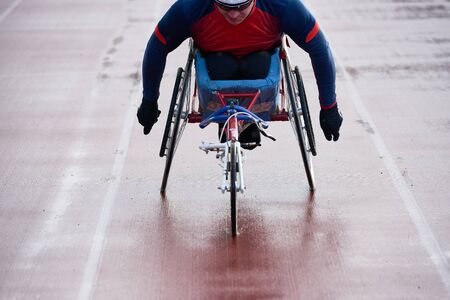 Performing feat in wheelchair. Close-up view of disabled sportsman in racing chair warming up alone on outdoor track before competition 스톡 콘텐츠