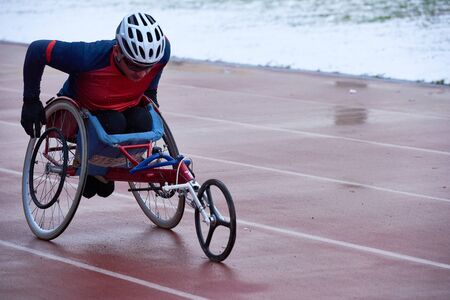 Strong-willed athlete in sportswear and helmet training in racing wheelchair