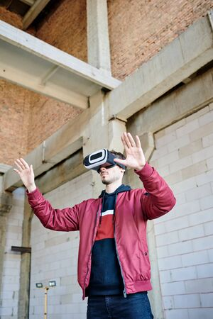 Young engineer in vr headset standing in front of virtual construction