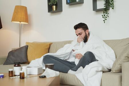 Sick man with flu or coronavirus sitting on couch in living-room and coughing Stockfoto