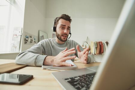 Young operator with headset explaining something during online consultation